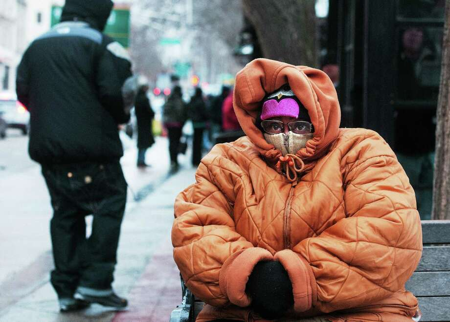 Tracey Copper of New Haven tries to keep warm as she waits for a bus after work early Thursday afternoon along Chapel Street. Copper was planning on getting home before the snowstorm began Thursday evening. Photo: Peter Casolino — New Haven Register