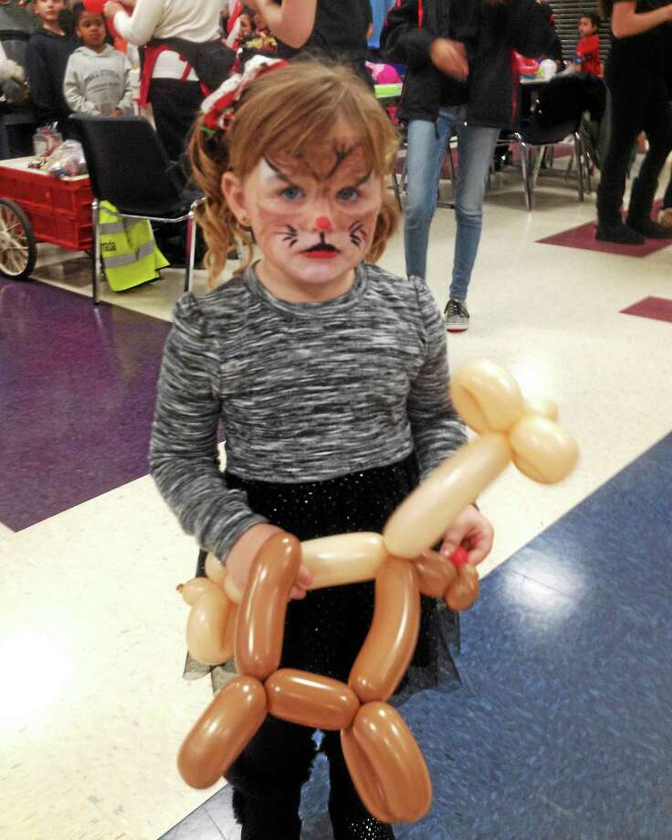 Children of all ages enjoyed watching — and receiving — their very own balloon creations courtesy of  Noodles at the holiday party organized by Cromwell Youth Services staff and Cromwell High School Student Council members. Photo: Jeff Mill — The Middletown Press