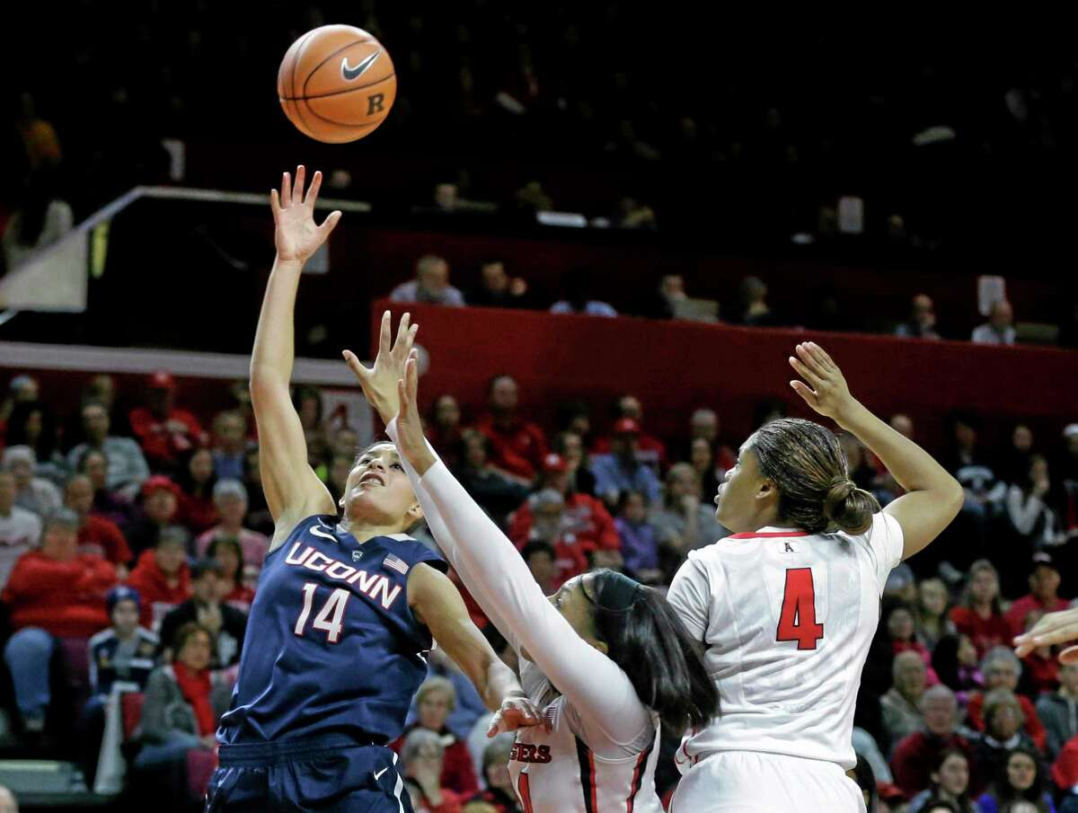 Connecticut guard Bria Hartley (14) takes a shot as she drives past Rutgers forward Betnijah Laney and guard Briyona Canty (4) during the first half of an NCAA women's college basketball game, Sunday, Jan. 19, 2014, in Piscataway, N.J. Hartley had 30 points in Connecticut's 94-64 win. (AP Photo/Mel Evans)