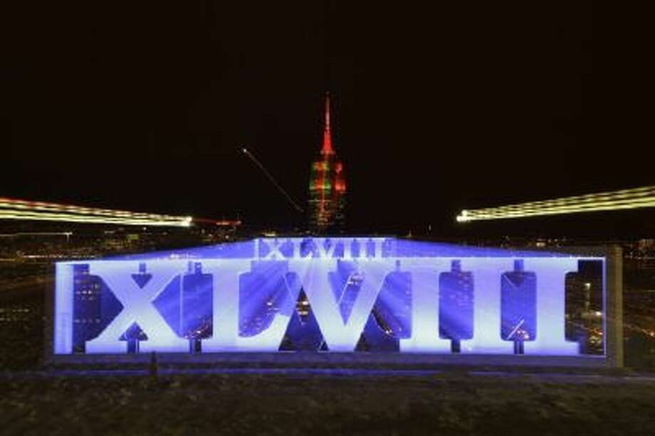 In this photograph taken while zooming out the lens during a long exposure, the Empire State Building, top, backdrops roman numerals for the NFL Super Bowl XLVIII football game at Pier A Park in Hoboken, N.J., Tuesday, Jan. 28, 2014. The Seattle Seahawks and the Denver Broncos are scheduled to play on Sunday, Feb. 2, 2014, at MetLife Stadium in East Rutherford, N.J.