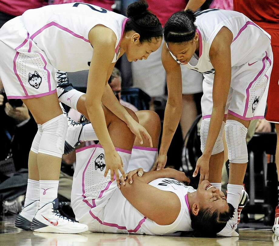 UConn's Kaleena Mosqueda-Lewis holds her arm after a hard fall to the court as teammates Saniya Chong, left, and Moriah Jefferson, right, look over her during the first half Sunday. Photo: Jessica Hill — The Associated Press  / FR125654 AP