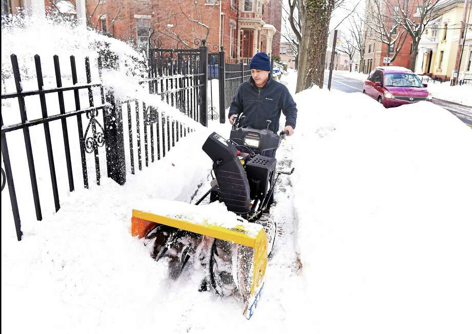 Walter Lapara clears snow from a sidewalk on Chapel Street in New Haven Monday. Photo: Arnold Gold — New Haven Register