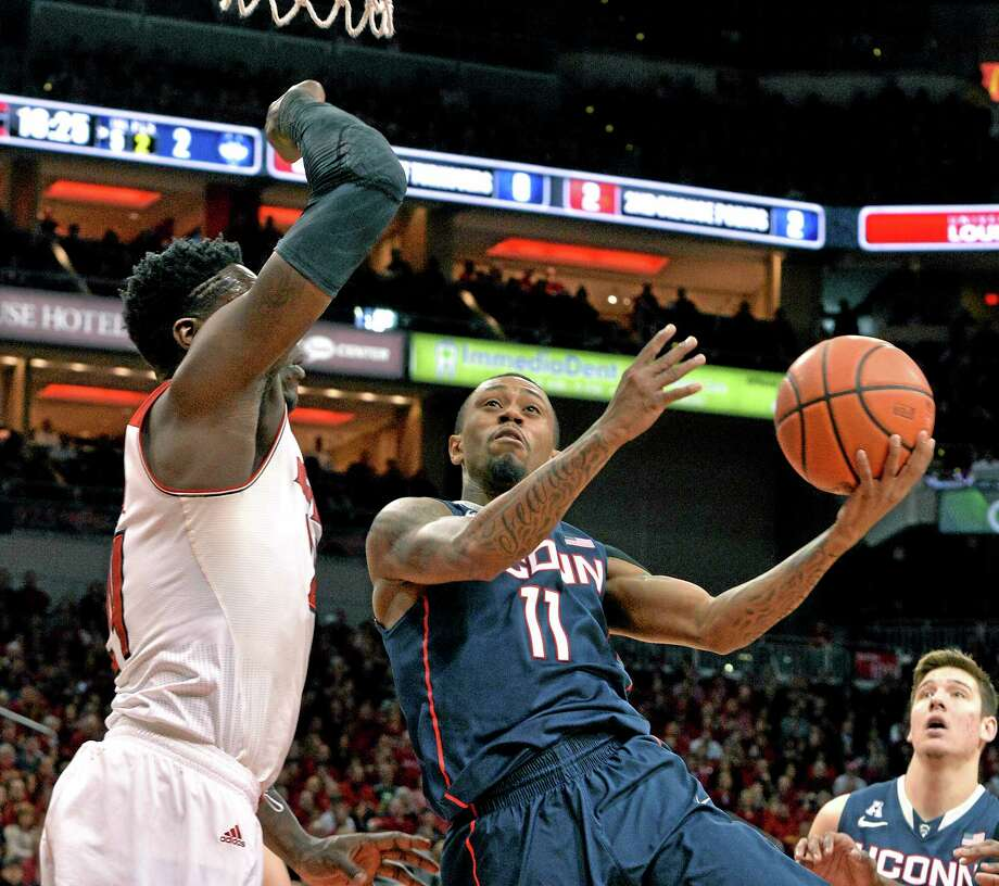 UConn's Ryan Boatright, right, attempts a shot over Louisville's Montrezl Harrell during the first half of the 19th-ranked Huskies' 81-48 loss to No. 11 Louisville on Saturday in Louisville, Ky. Photo: Timothy D. Easley — The Associated Press  / FR43398 AP