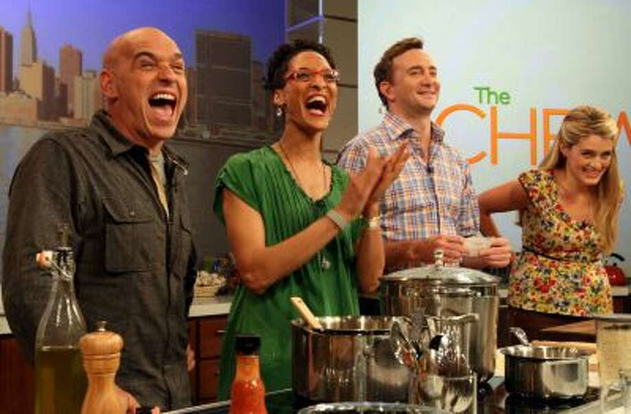 "This Friday, Aug. 26, 2011 photo shows co-hosts of ABC's ""The Chew"", from left to right, Iron Chef Michael Symon, Carla Hall, Clinton Kelly and Daphne Oz as they react to audience applause during a rehearsal of the show in New York. Can some of food and style TV's biggest stars help ABC soap fans get over cancellation of their favorite stories? The network's counting on it for ""The Chew.""   (AP Photo/Tina Fineberg) Photo: AP / AP2011"