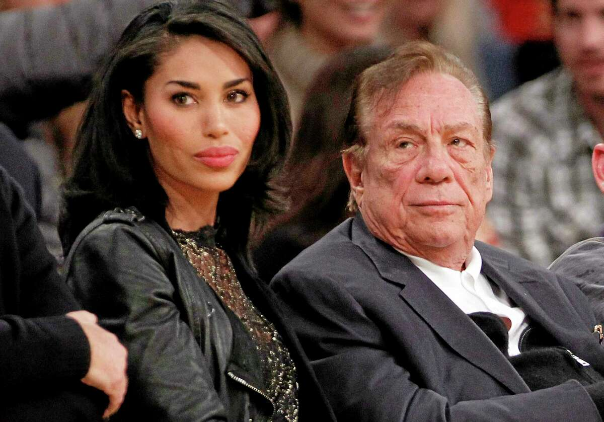 FILE - In this Dec. 19, 2010, file photo, Los Angeles Clippers owner Donald Sterling, right, and V. Stiviano, left, watch the Clippers play the Los Angeles Lakers during an NBA preseason basketball game in Los Angeles. NBA Commissioner Adam Silver has banned Sterling for life from the NBA and fined him the maximum $2.5 million. (AP Photo/Danny Moloshok, File)