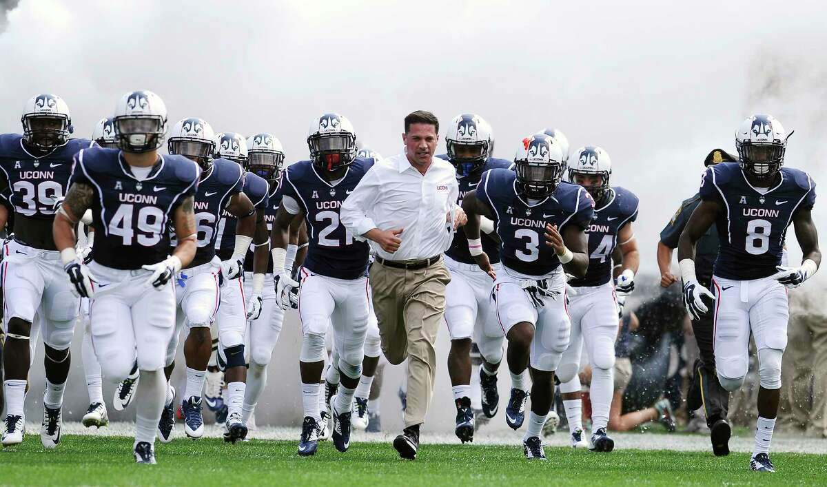UConn head coach Bob Diaco, center, runs on the field with his team at the start of Saturday's game against Stony Brook at Rentschler Field.