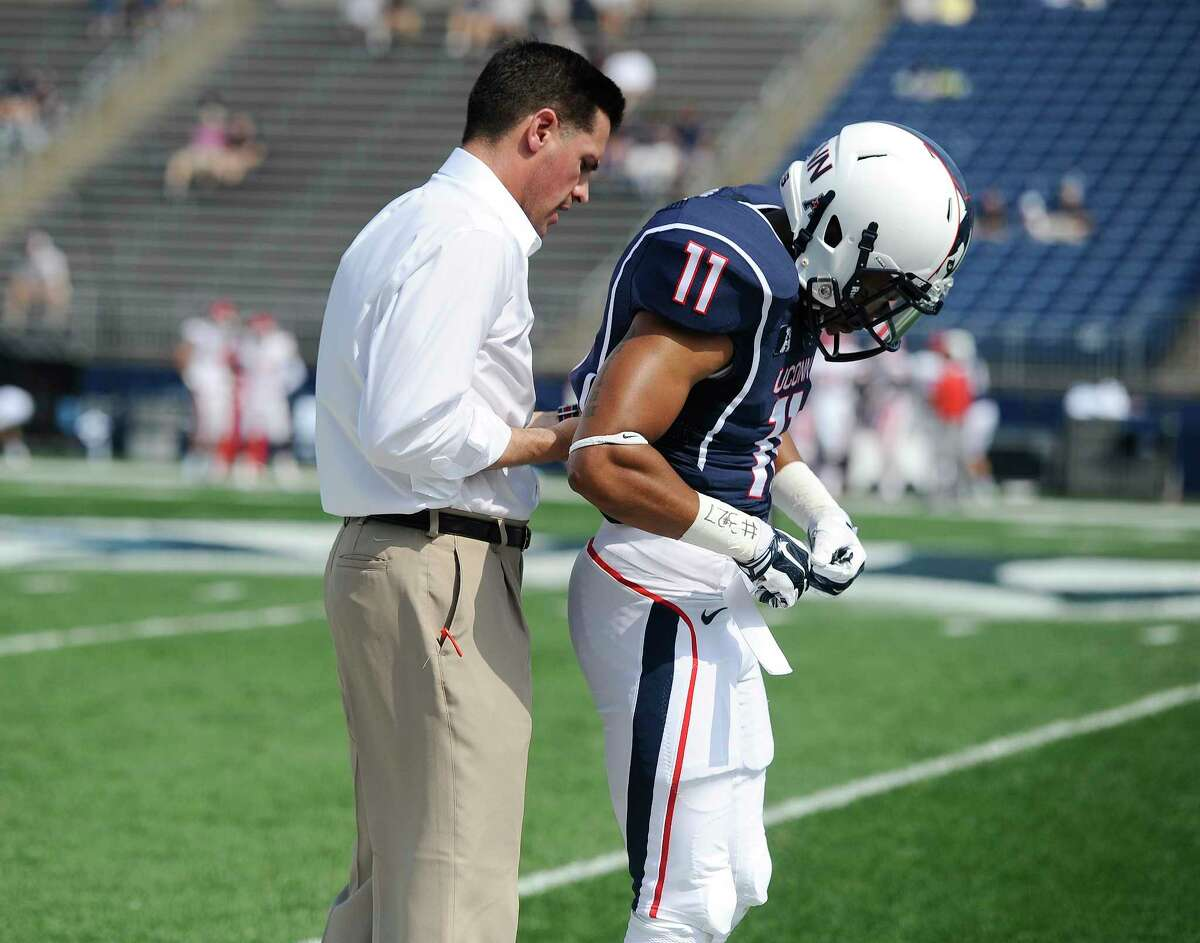 Connecticut head coach Bob Diaco, left, helps Connecticut cornerback Javon Hadley (11), right with his uniform before an NCAA college football game at Rentschler Field, Saturday, Sept. 6, 2014, in East Hartford, Conn. (AP Photo/Jessica Hill)