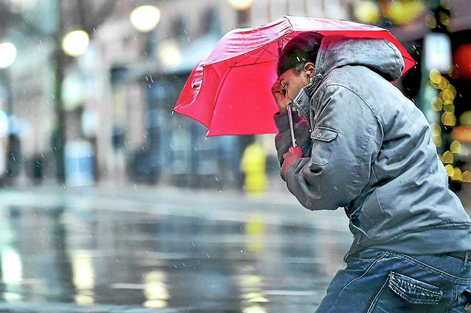 A pedestrian attempts to keep dry while battling winds gusts between 30 and 43 miles an hour in downtown New Haven Tuesday afternoon. Photo: Catherine Avalone — New Haven Register  / New Haven RegisterThe Middletown Press