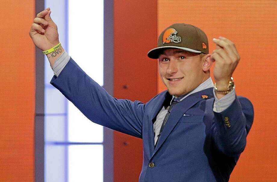 Texas A&M quarterback Johnny Manziel reacts after being selected by the Cleveland Browns as the 22nd pick in the first round of the NFL Draft on Thursday. Photo: Frank Franklin II — The Associated Press  / AP