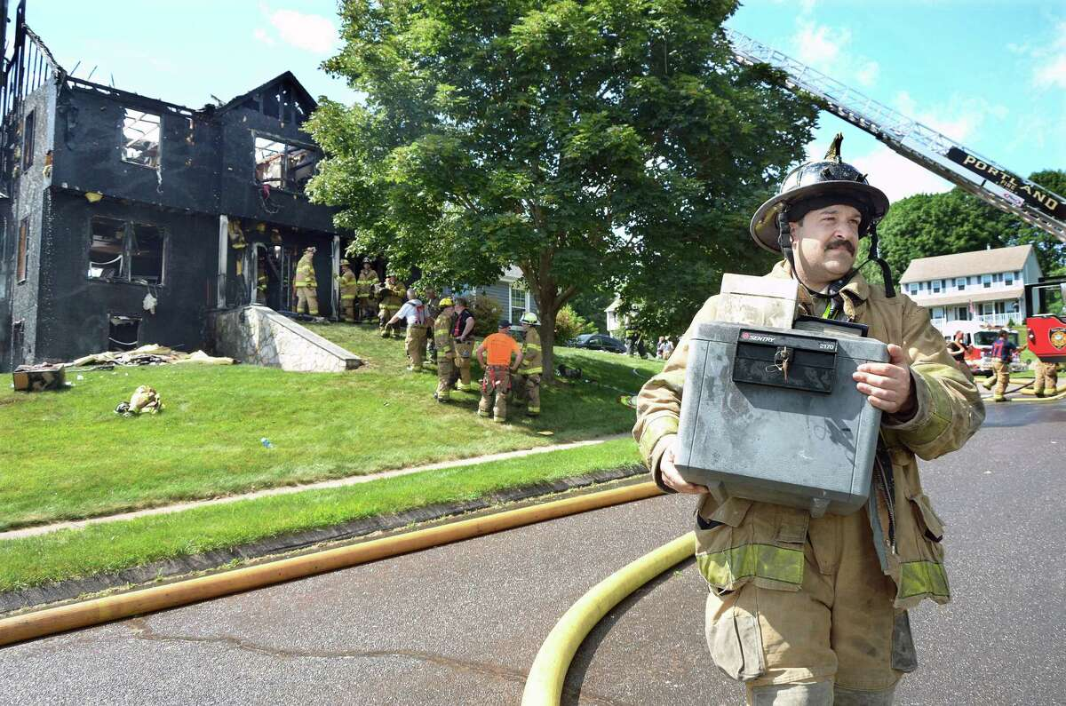 Catherine Avalone - The Middletown Press Portland's Deputy Fire Marshall Joe Scaglione carries out a safe following a fire that destroyed a home at 33 Belle Vista Heights in Portland Wednesday afternoon.