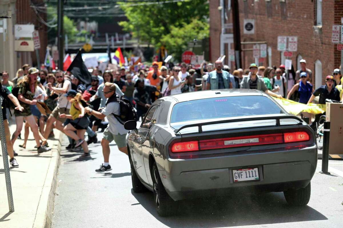 A vehicle drives into a group of protesters demonstrating against a white nationalist rally in Charlottesville, Va., Saturday, Aug. 12, 2017. The nationalists were holding the rally to protest plans by the city of Charlottesville to remove a statue of Confederate Gen. Robert E. Lee. There were several hundred protesters marching in a long line when the car drove into a group of them. /The Daily Progress via AP) ORG XMIT: VACHA101