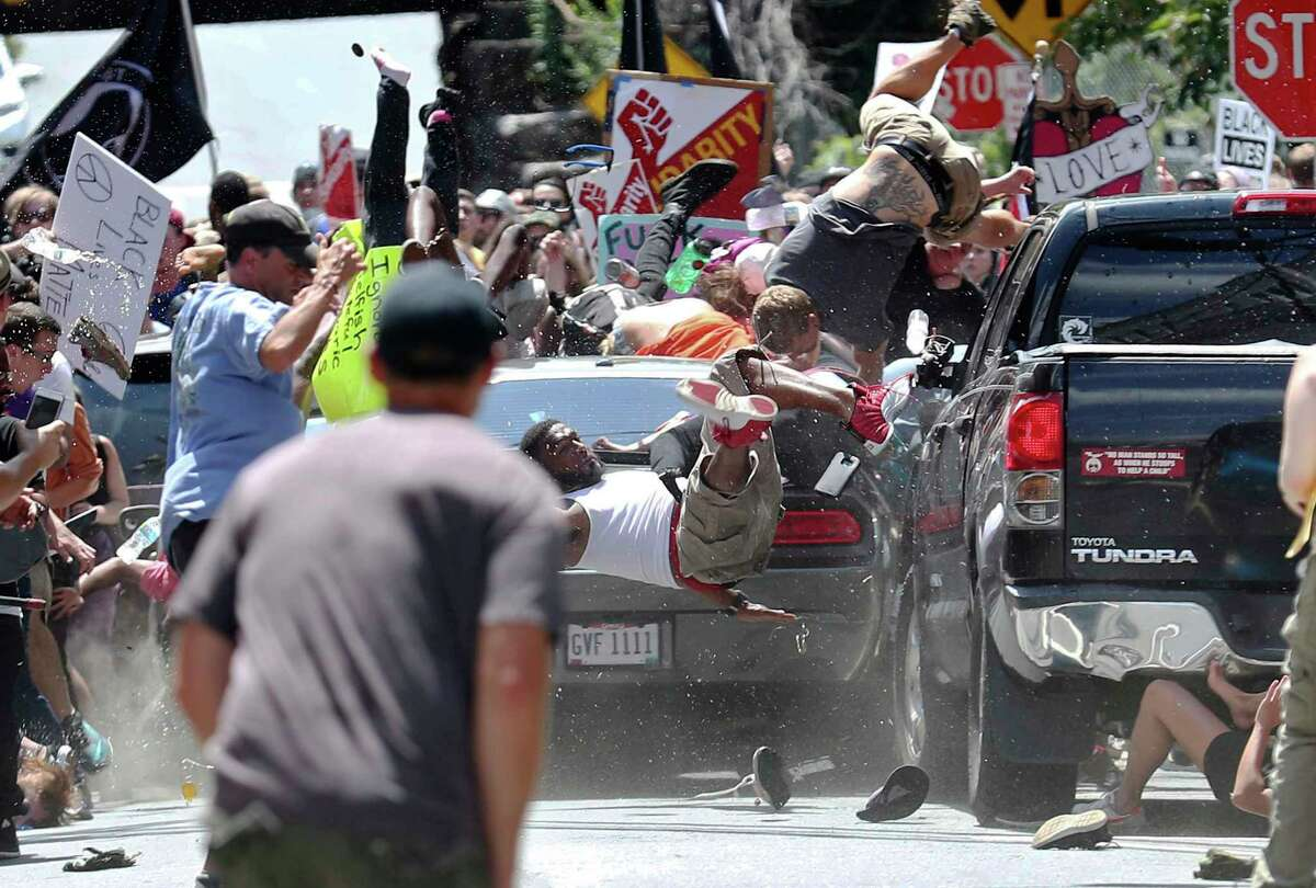 People fly into the air as a vehicle drives into a group of protesters demonstrating against a white nationalist rally in Charlottesville, Va., Saturday, Aug. 12, 2017. The nationalists were holding the rally to protest plans by the city of Charlottesville to remove a statue of Confederate Gen. Robert E. Lee. There were several hundred protesters marching in a long line when the car drove into a group of them. (Ryan M. Kelly/The Daily Progress via AP) ORG XMIT: VACHA103