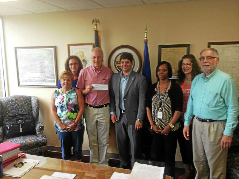 St. Vincent de Paul Executive Director Ron Krom, third from left, receives proceeds fromt the ninth annual Middletown mayor's ball. From left are St. Vincent board member Rochelle Hughes, city hall Executive Assistant Linda DeSena, Krom, Mayor Daniel Drew, city hall Administrative Assistant Sheila Jones, Councilwoman Sandra Russo-Driska and Councilman Robert Santangelo. Photo: Alex Gecan - The Middletown Press