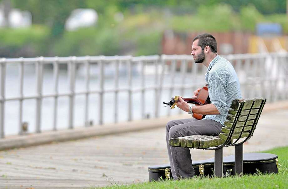 """Middletown resident Joseph Brayman plays the blues on his guitar at Harbor Park in Middletown Friday afternoon. Brayman said, """"It's a nice day to play by the river. Summer is coming to an end.""""  (Catherine Avalone - The Middletown Press) Photo: Journal Register Co. / TheMiddletownPress"""