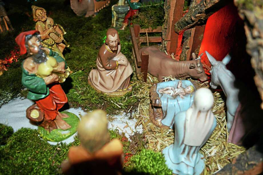 Mary and Joseph figurines kneel around the manger where the baby Jesus lies in this creche carefully constructed by Paul Antogiovanni of Middletown for his grandchildren on Christmas. Photo: Cassandra Day — The Middletown Press