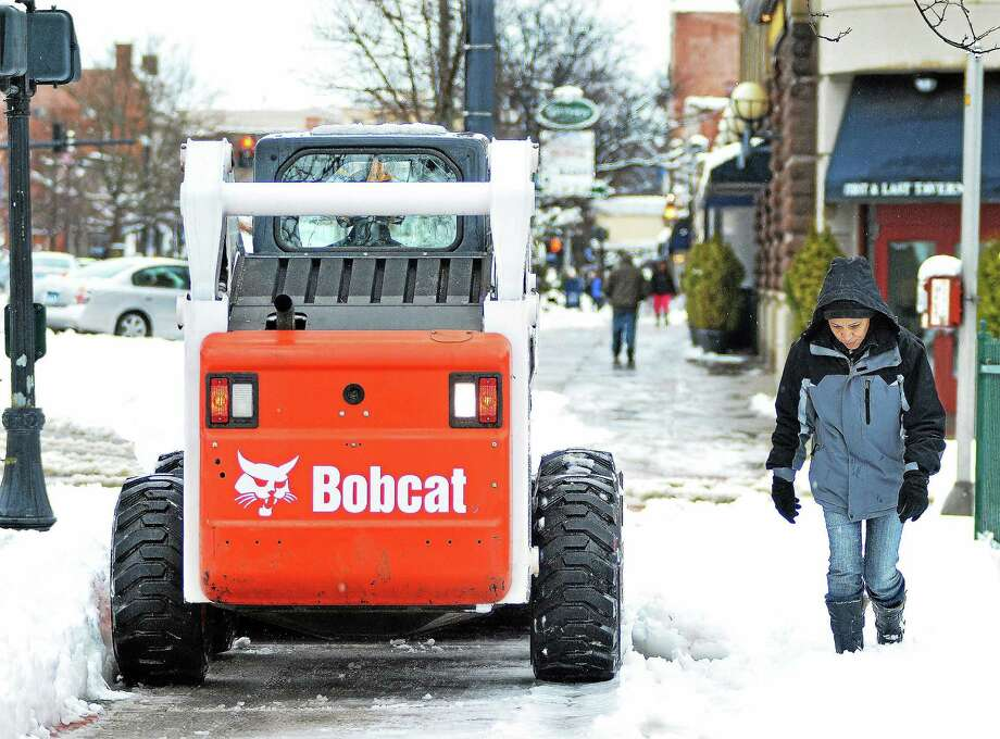 Plows and pedestrians shared the sidewalk  on Main Street in Middletown in this file photo. At the beginning of winter this year, public works officials are interviewing candidates to fill open slots for drivers. Photo: File Photo  / TheMiddletownPress
