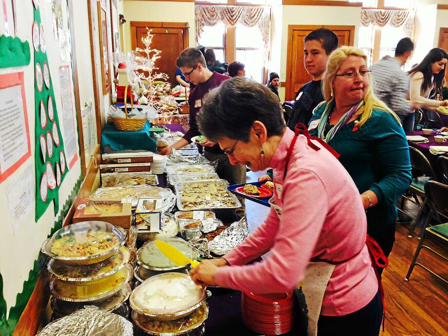 Volunteers assist with serving guests of the Community Christmas Dinner a bountiful feast last year at First Church of Christ on Court Street. Photo: File Photo