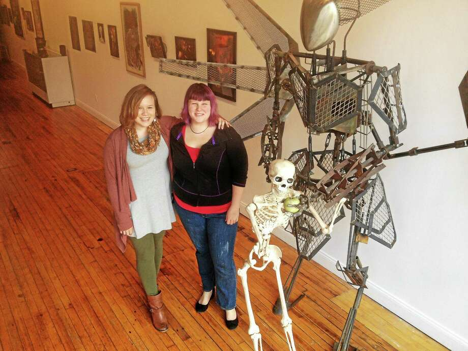 "Rachel Caldwell (left) and Jeanette Andriulli pose with Marcus Surrealis' ""Pre-Dystopian Angel,"" part of ""Inside the Monster Mind,"" running through Halloween at MAC650 in Middletown. Photo: Alex Gecan — The Middletown Press"
