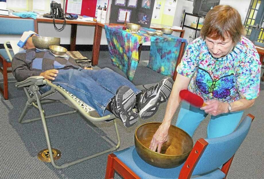 "CATHERINE AVALONE — THE MIDDLETOWN PRESS  Marie Menut, R.N., a vibrational healer from East Hartford, uses Tibetan singing bowls on staff and patients attending the 2012 Connecticut Valley Hospital Health Fair in this file photo. The singing bowls create a sound that is believed to improve physical, spiritual and emotional being. ""Each metal vibrates at its own rate,"" Menut said, ""and cells of our body relax to the vibration and react to the optimum rate."" Photo: Journal Register Co."