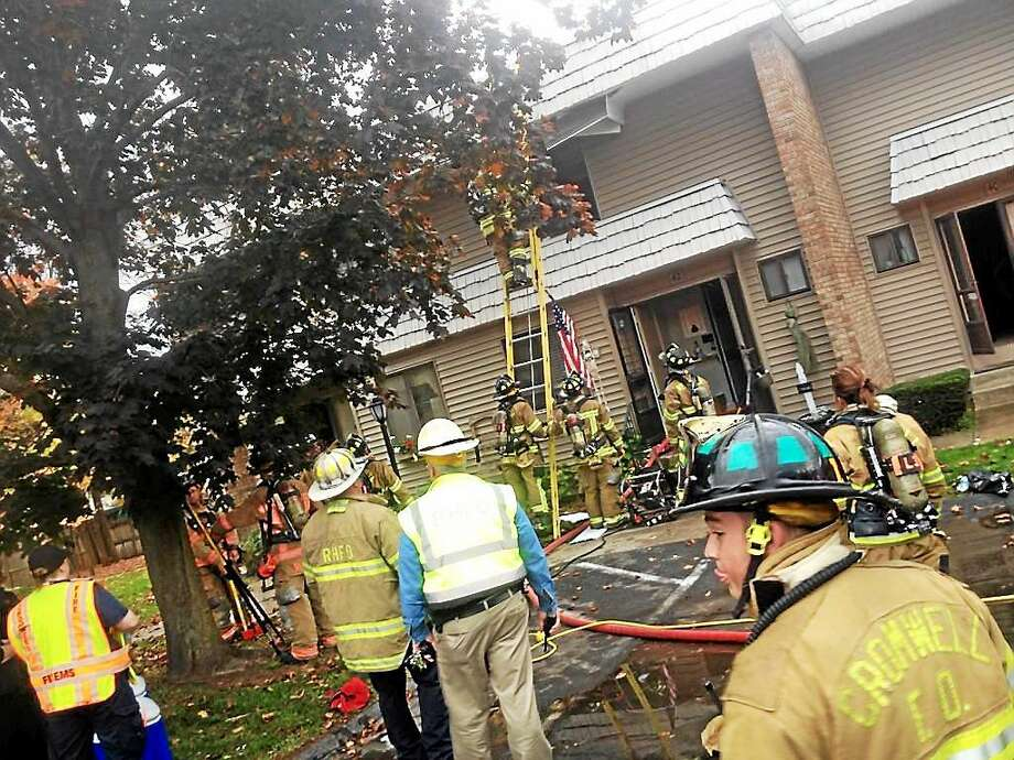 A two-alarm fire at a condominium on Cedarland Court in Cromwell was quickly extinguished Tuesday afternoon by firefighters from Cromwell, Rocky Hill and Middletown's Westfield volunteer company. Photo: Alex Gecan — The Middletown Press
