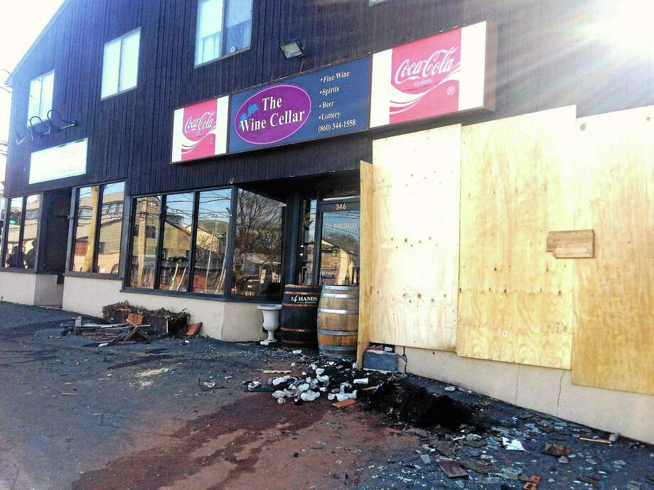 Alex Gecan - The Middletown Press Plywood covers the windows and barrels bar the entrance to The Wine Cellar at 346 South Main St. after a car plowed into the front of the building late Wednesday night. Photo: Journal Register Co.
