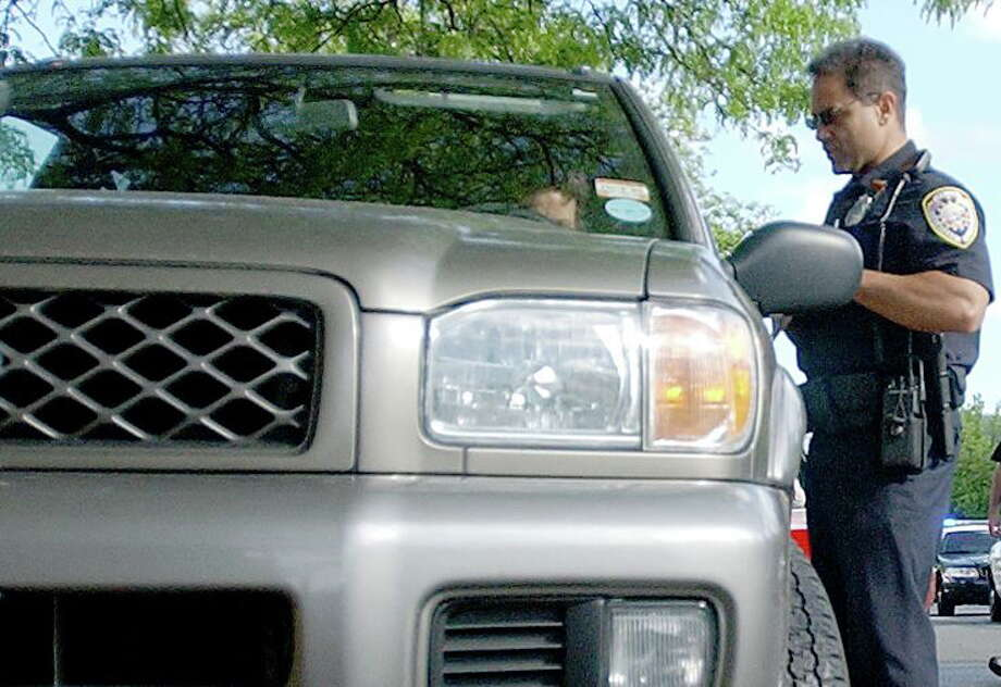 Former Middletown police officer Gino Pulvirenti tickets a motorist in this 2008 file photo. ¬ Photo: Middletown Press File Photo