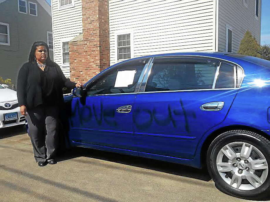 Lawanda Perry stands by her Nissan Altima, which has now sustained racist vandalism on at least two occasions. Her family painted the car blue after a prior attack. Perry said the vandals struck two nights in a row this week. Photo: Alex Gecan - The Middletown Press