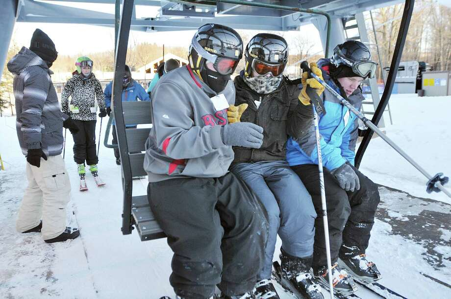 Nick Buono, lift operator, assists skiers at the chair lift at Powder Ridge in Middlefield Friday afternoon. Photo: Catherine Avalone — The Middletown Press  / TheMiddletownPress