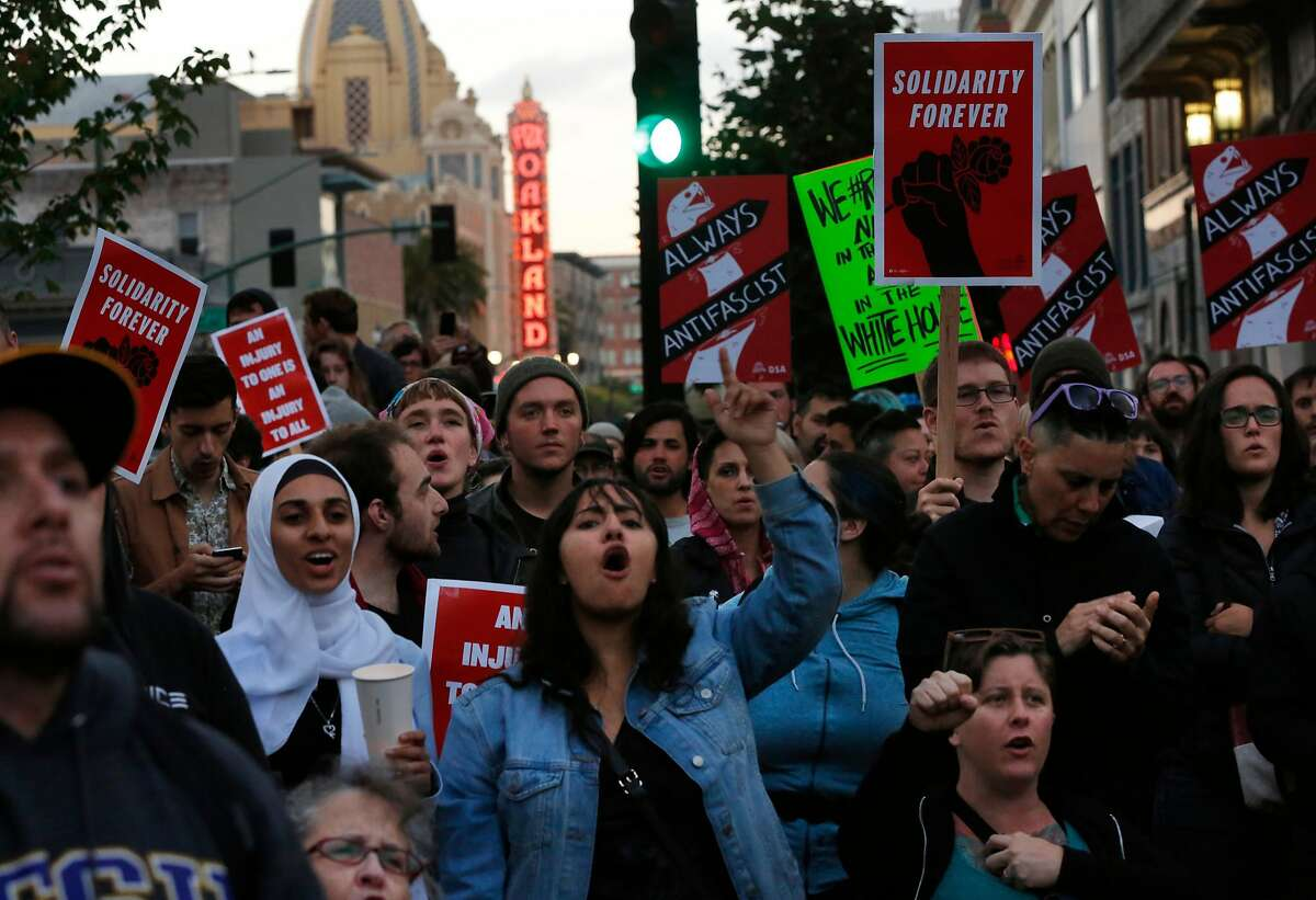 People cheer on a speaker during a Bay Area United Against White Supremacy rally in solidarity with Charlottesville August 12, 2017 in Oakland, Calif.