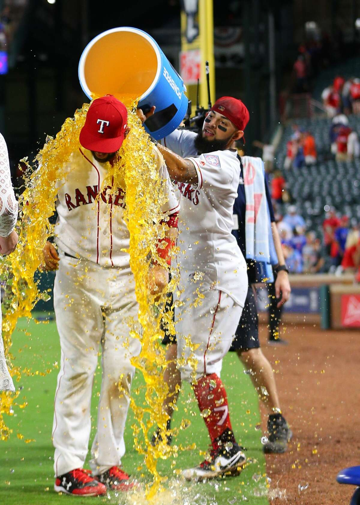 ARLINGTON, TX - AUGUST 12: Brett Nicholas #6 of the Texas Rangers gets the cooler dumped on him by Rougned Odor #12 at the conclusion of the game against the Houston Astros at Globe Life Park in Arlington on August 12, 2017 in Arlington, Texas. (Photo by Rick Yeatts/Getty Images)