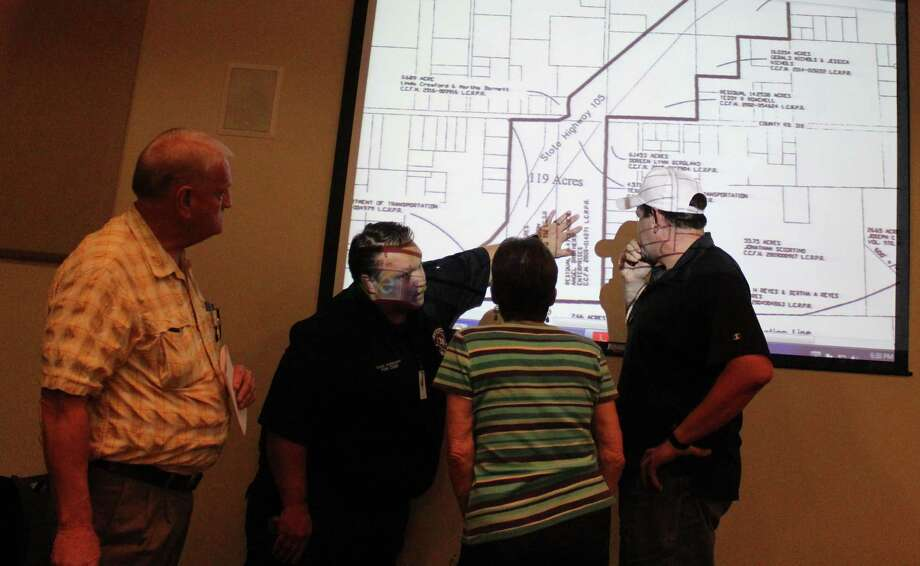 Cleveland Building Official Glen Barnhill (left) and Cleveland Fire Department Chief Sean Anderson (second from left) show on a projected map where the affected areas of the annexation are to two of Cleveland's citizens. Photo: Jacob McAdams