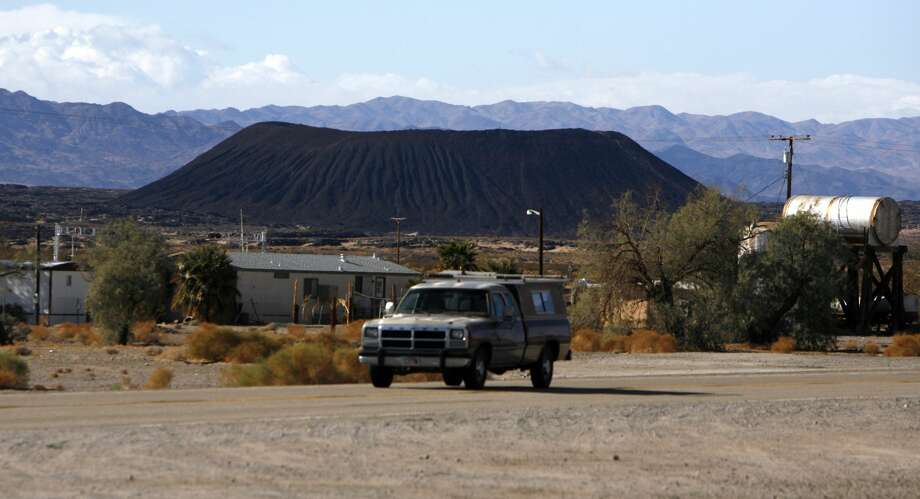 (Amboy,CA)–With Route 66 in the foreground, the Amboy Crater rises above the desert floor reminding tourists of the volcanic history of the area.There was a time when Amboy was a popular stop on Route 66. Gas was expensive and the malts were cold at Roys, the only cafe in town. Today Roys is closed and the town was purchased by businessman Albert Okura. About 4 people live there including caretaker Larry Stevens, 55, who wears a black cap and often sells a couple of gallons of gas to motorists. Stevens and his two dogs watch the town, and will someday start the rennovation. December 27, 2006  (Photo by Mark Boster/Los Angeles Times via Getty Images) Photo: Mark Boster/LA Times Via Getty Images