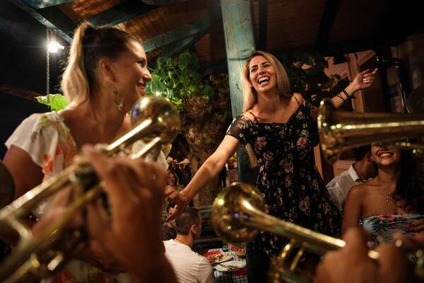 GUCA, SERBIA - AUGUST 11: Revellers dance as a brass band plays in a restaurant during the Guca Trumpet Festival on August 11, 2017 in Guca, Serbia. Thousands of revellers attend the trumpet festival, held annually since 1961 in the small, central Serbian town of Guca. The free event is a celebration of Balkan music with dozens of orchestras and solo trumpeters taking part in the festival's main competition. During the festival wild street parties take place throughout the night as brass bands parade and play for tips to the thousands of visitors in the town's restaurants, bars and pop-up tents. (Photo by Jack Taylor/Getty Images)