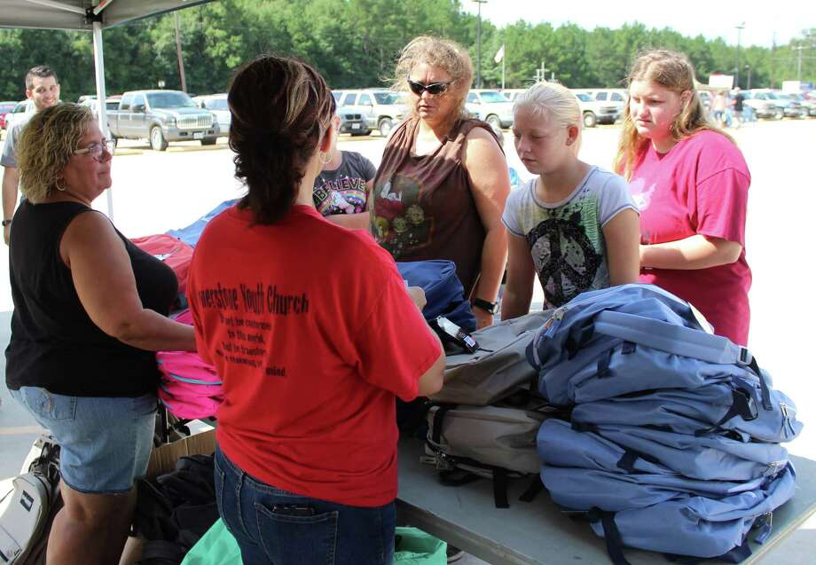 Hazel Kersh (left) and Shelaine Asfour (right) give out backpacks for students at the Cornerstone Church Back to School Backpack Bash on Aug. 12. Photo: Jacob McAdams