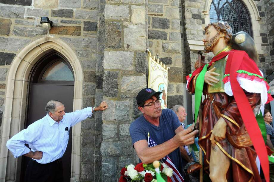 Greenwich resident Richard Roesler pins money onto the statue of St. Roch during the annual St. Roch Feast closing procession in Greenwich, Conn. on Sunday, August 13, 2017. Photo: Michael Cummo / Hearst Connecticut Media / Stamford Advocate