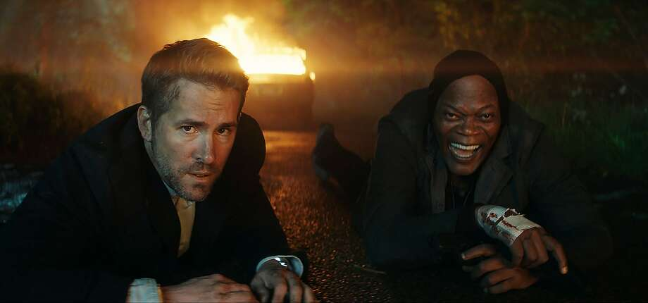 Ryan Reynolds (left) plays an ex-CIA agent protecting a hit man (Samuel L. Jackson) who is to testify against a war criminal. Photo: Associated Press