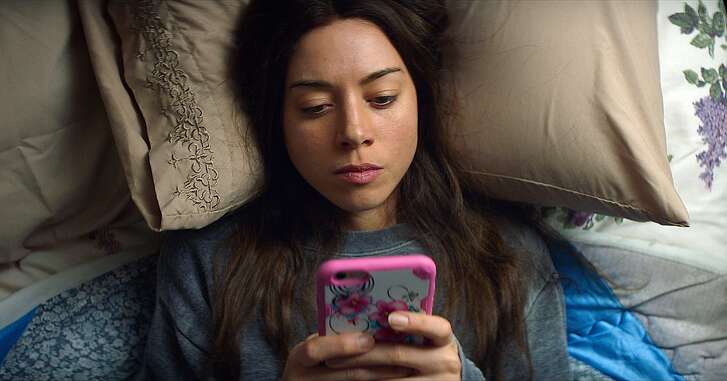 """This image released by Neon shows Aubrey Plaza in a scene from, """"Ingrid Goes West."""" Plaza plays a woman who becomes obsessed with a woman on Instagram, played by Elizabeth Olsen. She goes so far as to start dressing and acting like her and eventually even befriends her social media idol. (Neon via AP)"""