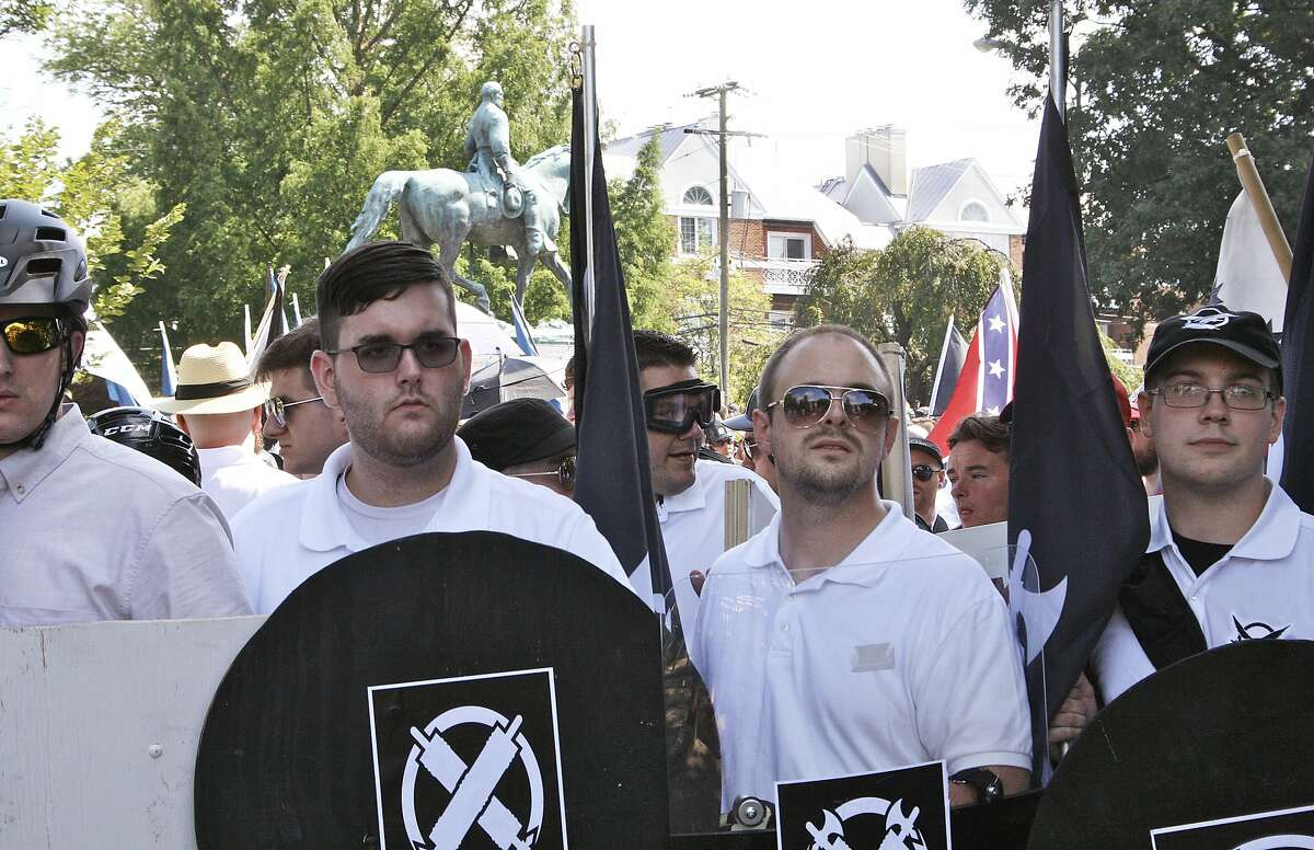 In this Saturday, Aug. 12, 2017 photo, James Alex Fields Jr., second from left, holds a black shield in Charlottesville, Va., where a white supremacist rally took place. Fields was later charged with second-degree murder and other counts after authorities say he plowed a car into a crowd of people protesting the white nationalist rally. (Alan Goffinski AP)