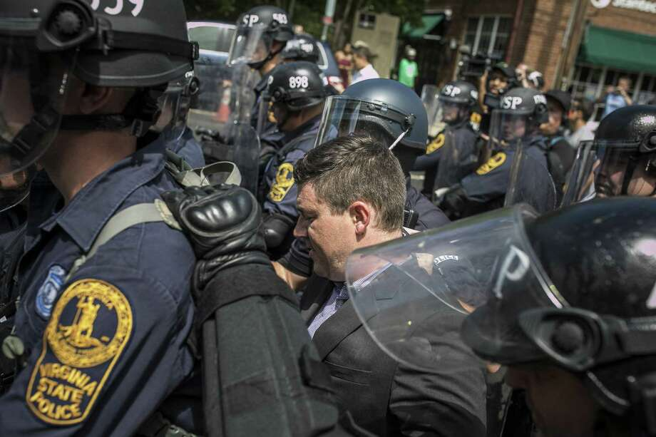 Jason Kessler, organizer for Unite the Right, a gathering of white nationalists, is escorted away from his news conference after he was punched, at City Hall in Charlottesville, Va., Aug. 13, 2017, The incident comes the day after a rally and counter-protests in the city resulted in violence, injuries and a death. (Edu Bayer/The New York Times) Photo: EDU BAYER, STR / NYT / NYTNS
