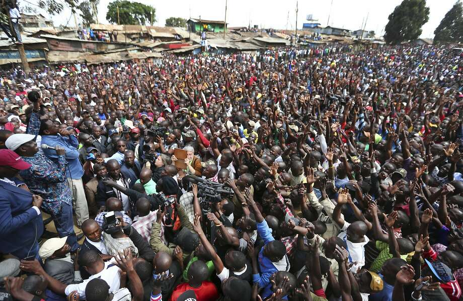 Opposition leader Raila Odinga (left) speaks into a microphone as he addresses supporters in the Kibera area of Nairobi, Kenya. Odinga alleges that election rigging cost him the presidency. Photo: Brian Inganga, Associated Press