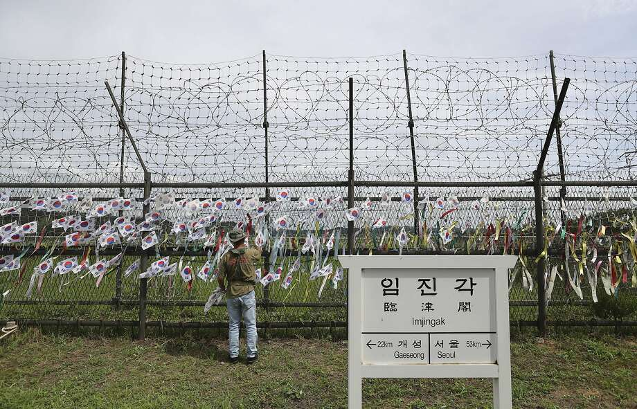 A man adjusts national flags on a fence near the demilitarized zone in Paju, South Korea. Photo: Lee Jin-man, Associated Press
