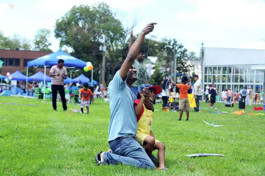 Stamford residents Raja Konda and Lakshman Konda, 4, work together to get their kite off the ground during the India Day Festival at Mill River Park in Stamford, Conn. on Sunday, August 13, 2017. Photo: Michael Cummo / Hearst Connecticut Media / Stamford Advocate