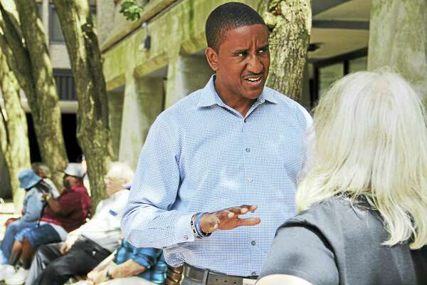 Marcus Paca speaks to a woman during a canvassing event at Bella Vista Apartments this month in New Haven.