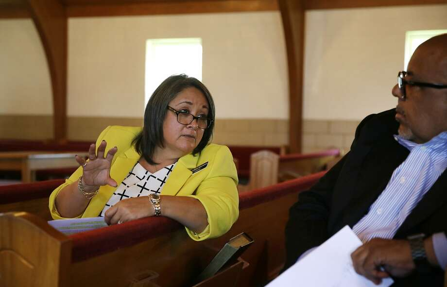 Melissa Zenteno, chaplain at One Safe Place in Forth Worth, Texas, tells Pastor Bruce Datcher about her group's programs to help domestic violence victims. Photo: LM Otero, Associated Press