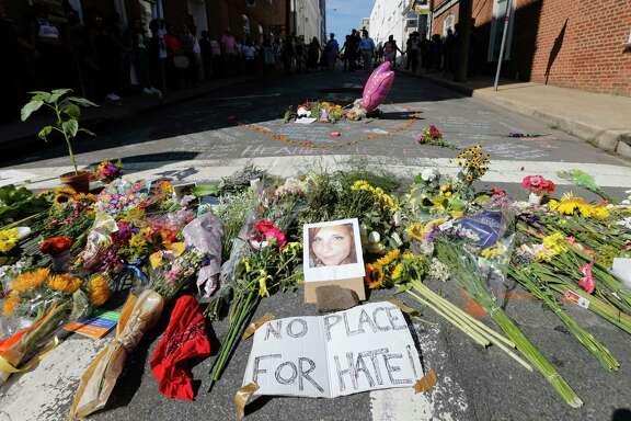A memorial of flowers and a photo of the fatal victim, Heather Heyer, sits in Charlottesville, Va., Sunday. Heyer died when a car rammed into a group who were protesting the presence of a white supremacist rally.