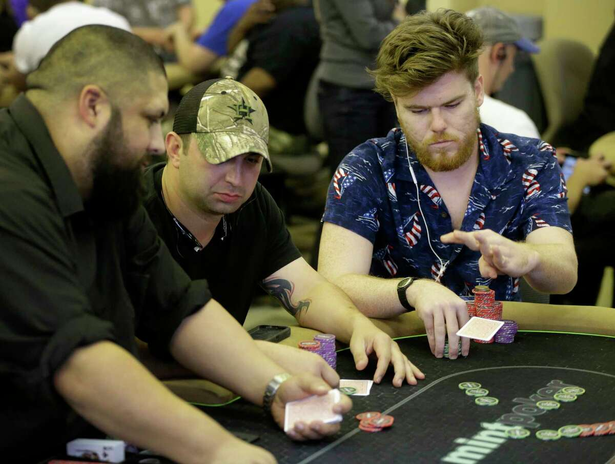 Dealer Richard Pope, left, mans the table as Court Manuel, center, and Ed Wanson, play at Mint Poker, Houston's first restricted membership-based poker club.