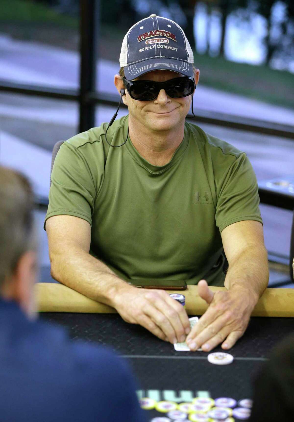 John Cornelius of Deer Park checks his cards during game at Mint Poker, which charges players a membership fee but doesn't take any share of the pots.