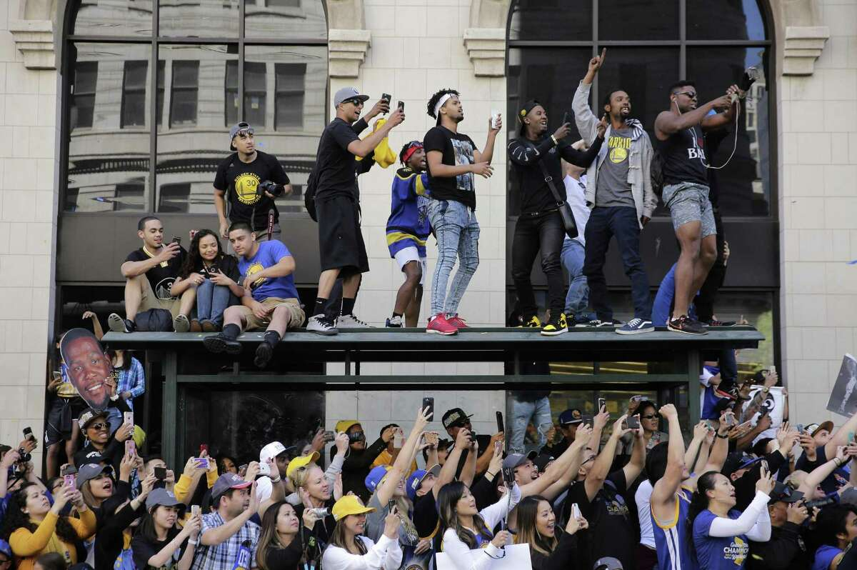 Fans scramble for a good look Golden State Warriors during the basketball team's victory parade through downtown Oakland in June.