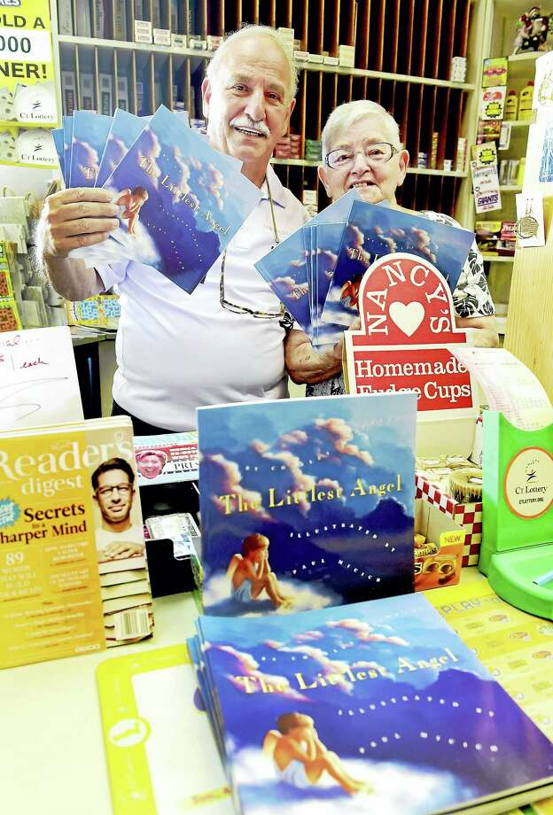 "(Peter Hvizdak - Hearst Connecticut Media) Branford, Connecticut: August 4, 2017.  Bobby Esposito, owner of Branford Book & Card Shoppe and employee Roseann (CQ) Barontini hold copies of the book ""The Littlest Angel"" by Charles Tazewell at the shop Friday on Main Street in Branford.  Following the drowning of 10-year-old Ben Callahan, an anonymous Branford woman is donating 330 free copies of the book to be distributed around town as a way of helping children cope with Callahan's death by understanding death and faith. Copies of the book have also been donated to Branford libraries, churches and the YMCA. / New Haven Register"