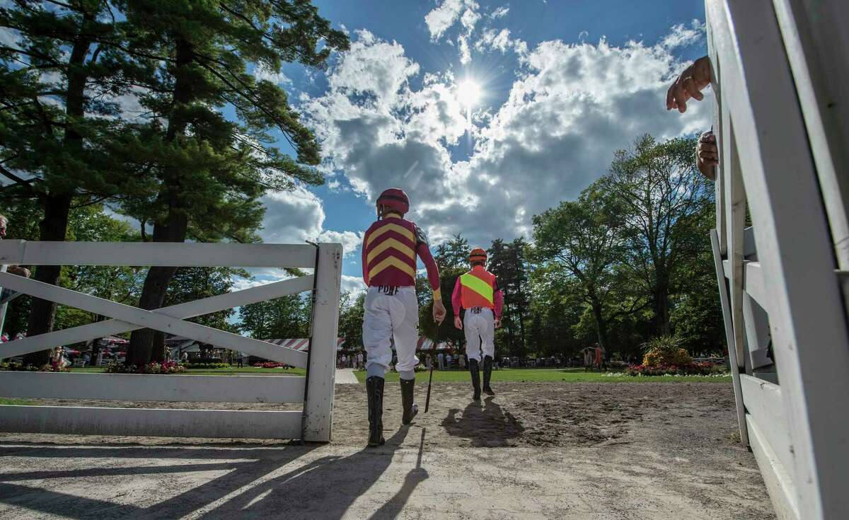 Jockeys walk to the paddock for the 7th race on the card with beautiful clouds above at the Saratoga Race Course Sunday Aug. 13, 2017 in Saratoga Springs, N.Y. (Skip Dickstein/Times Union)